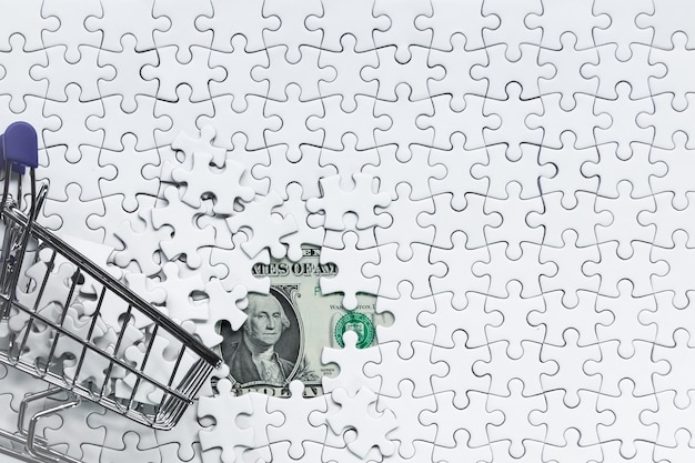 Side shopping cart full of jigsaw puzzle on money dollar background, business solution concept ,key for success