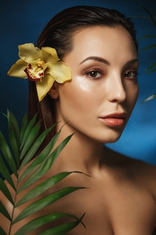 Side shot of attractive woman standing behind exotic flowers.