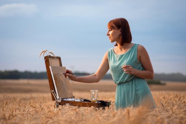일몰 동안 호밀밭에서 그림을 그리는 여성 예술가의 측면 샷