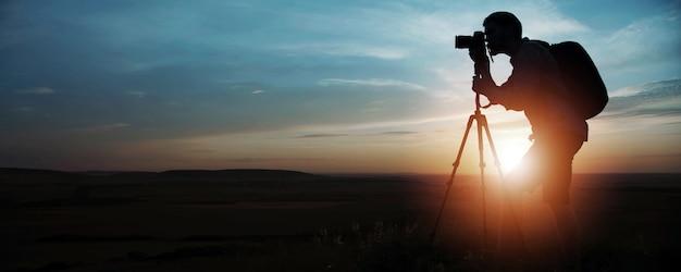 日没または日の出にデジタル一眼レフカメラと三脚を使用して写真を撮る写真家の側面のシルエット