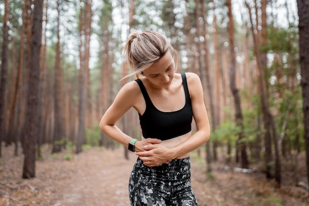 Side stitch woman runner side cramps after running. jogging woman with stomach side pain after jogging work out. female athlete. sport, health and people concept.