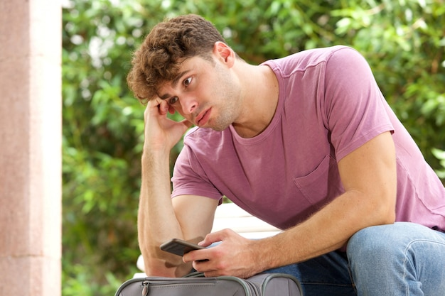 Side of stressed man sitting on park bench with suitcase and cellphone