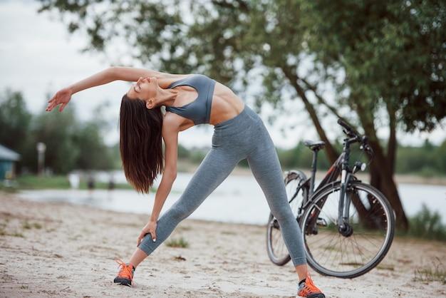 サイドストレッチ。昼間にビーチで彼女の自転車の近くのヨガの練習をしている良い体型の女性サイクリスト