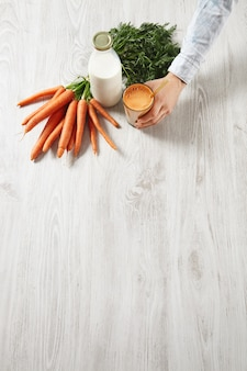 Вид сбоку сверху на деревянный стол, урожай моркови на ферме, лежащий возле бутылки, и рука человека держит стакан, наполненный смесью натурального свежего сока и молока с золотой трубочкой для питья в нем