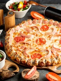 Боковой вид колбасной пиццы с сыром и помидором