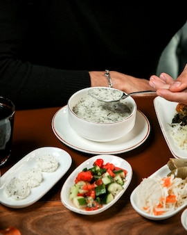 Side vie of traditional azerbaijan yogurt soup dovga in a white bowl with pita on the table