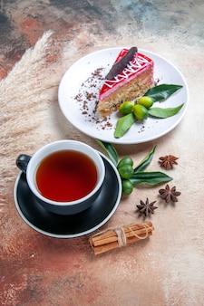 Вид сбоку чашка чая черная чашка чая корица звездчатый анис тарелка торта