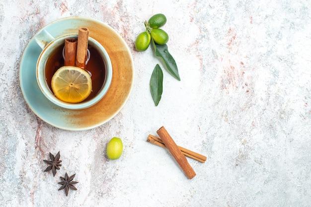 ピンクのテーブルに柑橘系の果物とシナモンスティックが付いた受け皿にレモンとシナモンのスライスが入ったハーブティーのティーカップの側面図