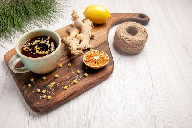 トウヒの枝の横にある木製のキッチンボード上のハーブティーレモンのお茶の白いカップの側面図