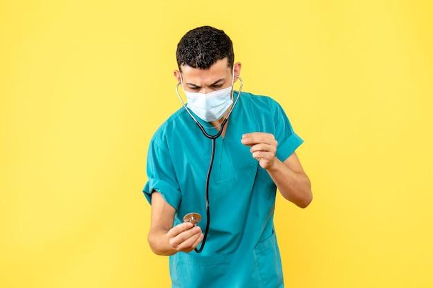 Вид сбоку врач в маске с фонендоскопом рассказывает о лечении covid-
