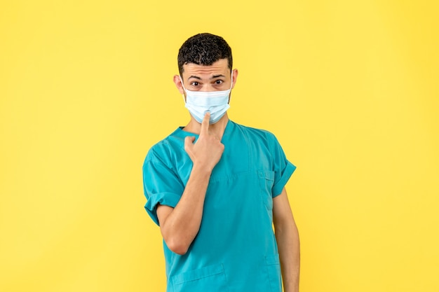 Вид сбоку доктор в маске доктор указывает на медицинскую маску