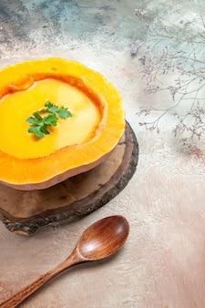 Вид сбоку суп из тыквы с травами на доске рядом с ложкой веток дерева