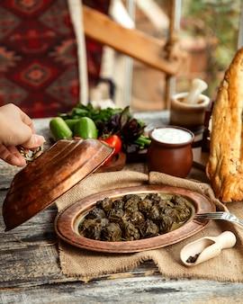 Вид сбоку на традиционное азербайджанское блюдо мясная долма из виноградных листьев с йогуртом и овощами
