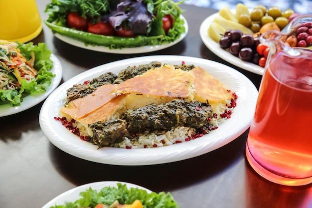 Вид сбоку на традиционное азербайджанское блюдо сябзи плов из мяса с зеленью и отварным рисом на тарелке с компотом