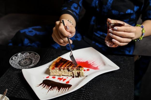 Вид сбоку женщина ест чизкейк с шоколадным сиропом и пьет чай в бокале армуду