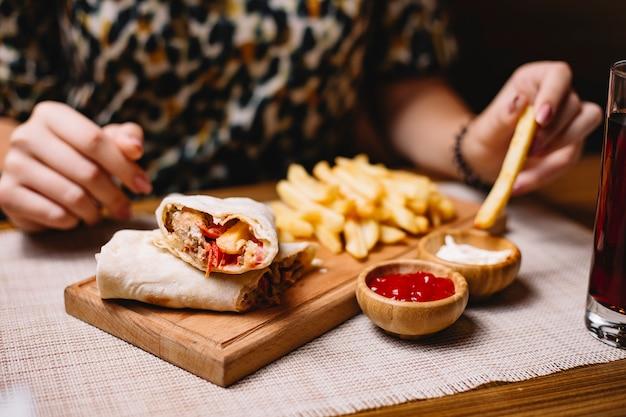 Вид сбоку женщина ест куриного донера в лаваше с картофелем фри с кетчупом и майонезом