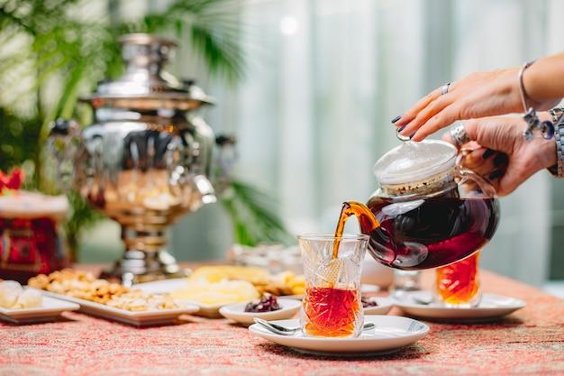 Вид сбоку женщина наливает чай из чайника в стакан армуда на блюдце