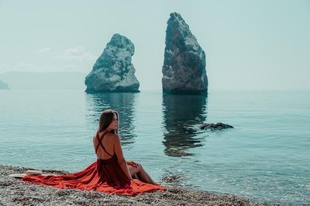 海の近くでポーズをとっている赤い長いドレスを着た若い美しい官能的な女性の側面図