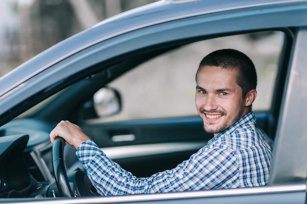 Вид сбоку. молодой человек сидит за рулем автомобиля. крупным планом.