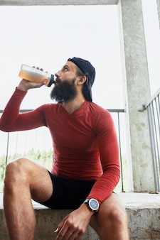 Side view of active bearded sportsman drinking water from glass bottle while having rest and sitting on stairs in bright day.