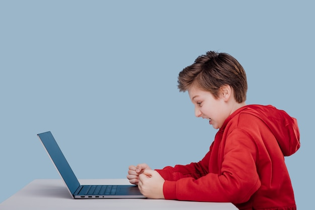 Side view of addicted furious child boy in red sweatshirt playing game on laptop at table in studio ...