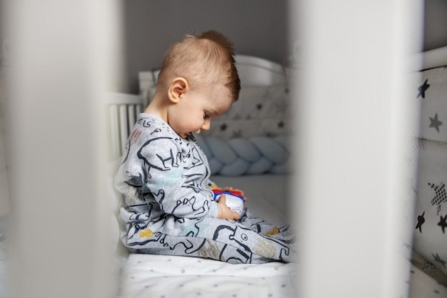 Side view of adorable blond little baby boy sitting in his crib in the morning and exploring new car toy.