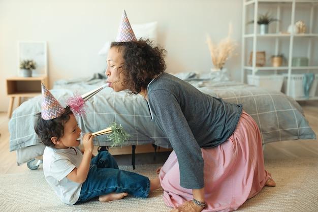Vista laterale del ragazzino felice adorabile che si siede sul pavimento con la sua giovane madre che porta il cappello del cono, che soffia fischietti