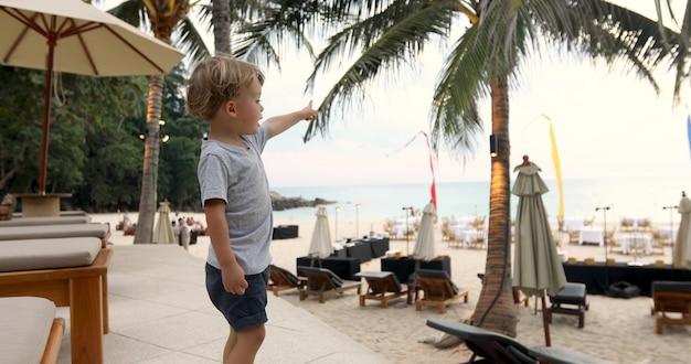 Side view of adorable little boy in t-shirt and shorts pointing at sea while standing near loungers on beach on resort