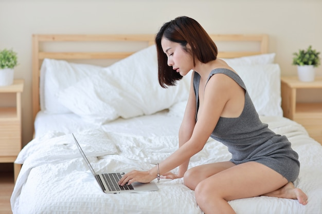 Side view of adult freelance asian woman working on computer and cell phone on bed in bedroom