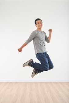 Side view of adult man bouncing high in the air