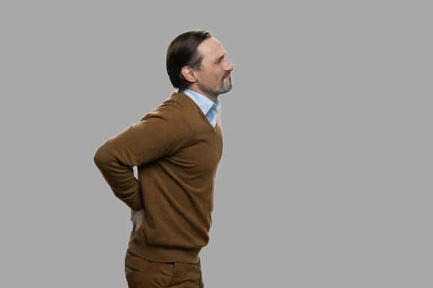 요통으로 고통받는 측면보기 성인 남자. 회색 배경에 서있는 동안 요통으로 고통받는 불행한 성숙한 남자.