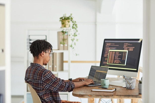 Side view at african-american it developer typing on keyboard with black and orange programming code on computer screen and laptop, copy space