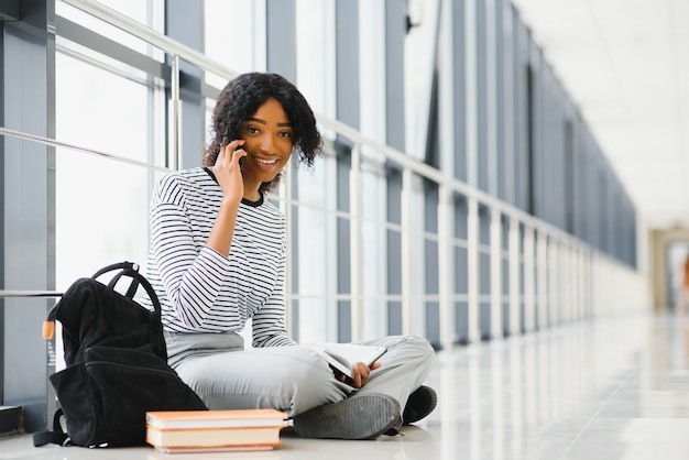 Side view of african american student sitting on floor and reading book in corridor