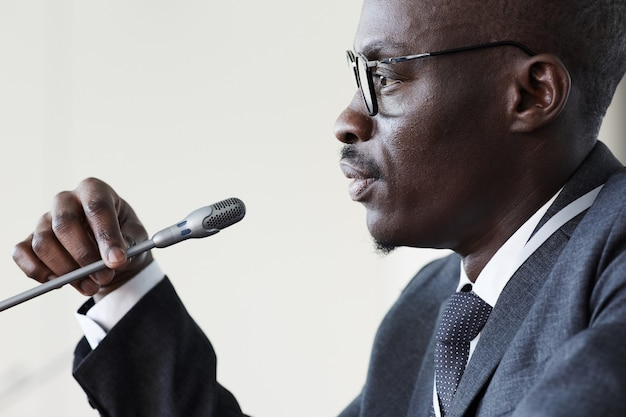 Side view of african businessman speaking in microphone at business conference