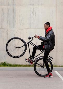 アフリカ系アメリカ人の男性と彼の自転車の側面図