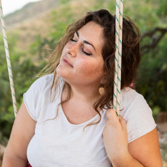 Side view of alluring woman outdoors in swing