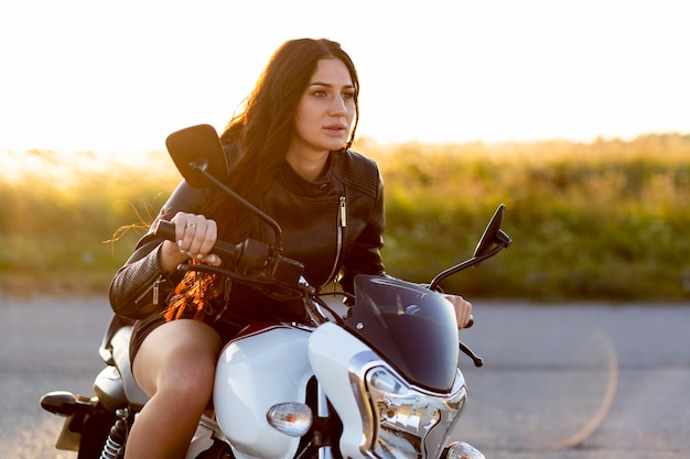 Side view of alluring woman riding her motorcycle