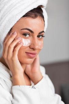 Side view of alluring woman using under eye patches