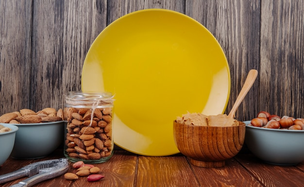 Side view of almond in a glass jar and a bowl with peanut butter in a bowl and yellow ceramic plate at wooden background