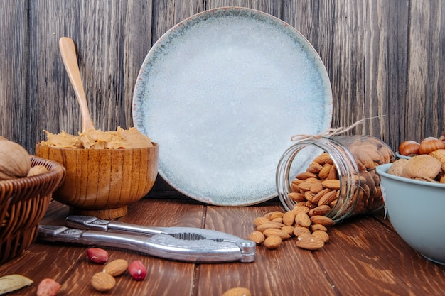 Side view of almond scattered from a glass jar and a bowl with peanut butter on wooden background