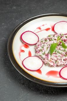 皿にソースをかけた大根とハーブの食欲をそそる料理の側面図
