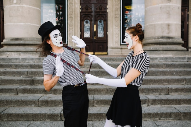 Side view of a angry female mime pulling male mime suspender in front of stairway