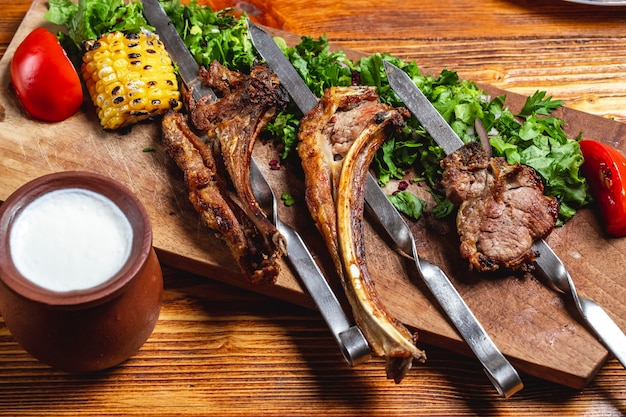 Side view antricot kebab grilled lamb ribs with greens red onion tomato grilled corn and yogurt on the table