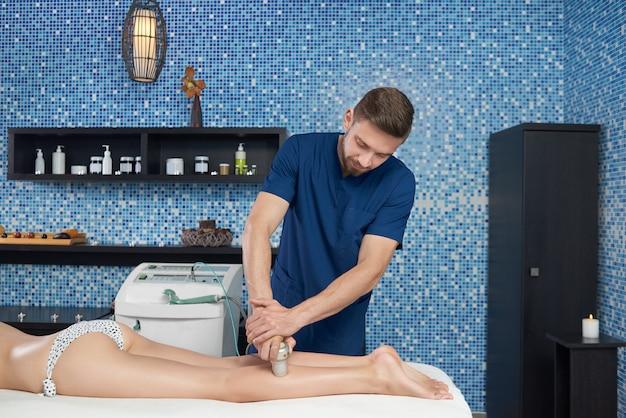 Side view of apparatus massage procedure of legs in salon