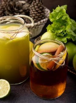 Вид сбоку яблоко пьет свежий яблочный сок и лимонный чай с лаймом, корицей, зеленым яблоком и салатом на черной доске