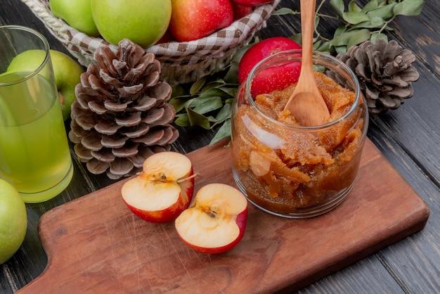 Vista laterale della marmellata di mele in barattolo di vetro con un cucchiaio di legno e mezza mela tagliata sul tagliere con succo di mela cesto di mele pigne e foglie su superficie di legno