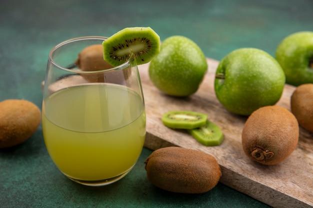 Vista laterale del succo di mela in un bicchiere con mele verdi e kiwi su una tavola su uno sfondo verde
