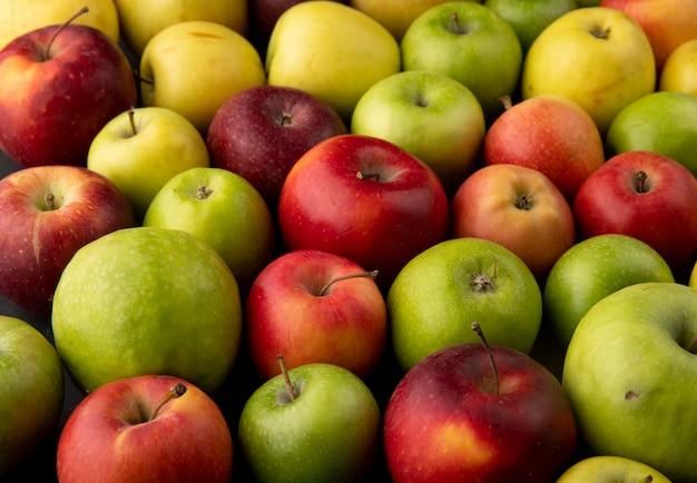 Вид сбоку яблочный микс зеленые желтые и красные яблоки фон