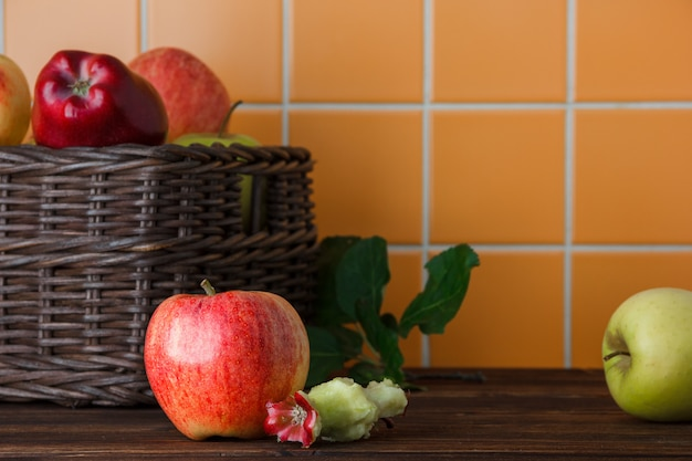 Side view apples in basket with bitten one on wooden and orange tile background. horizontal