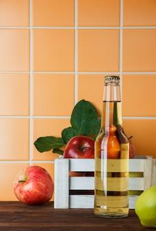 木製とオレンジ色のタイルの背景のボックスにリンゴジュースと側面図リンゴ。テキストの垂直方向のスペース